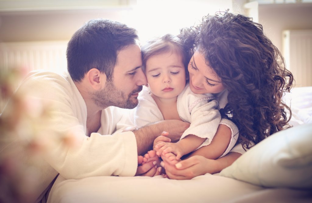 Family with baby laying in bed